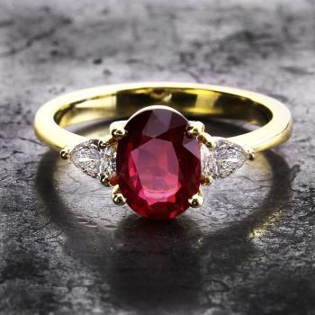 trilogy ring with an oval ruby flanked by two pear shaped diamonds set with claws