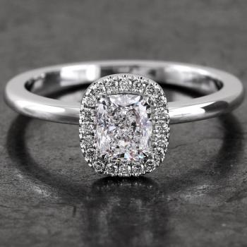 halo ring with a central cushion cut surrounded by accent stones in castle pavé setting mounted on a bird-shaped or hollow V on a slightly convex band set with a small diamond on the side (compatible with a wedding ring)