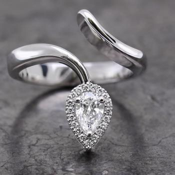 halo ring with pear cut diamond surrounded by smaller brilliant cut diamonds