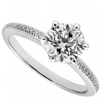 solitaire ring with a central brilliant in six prongs on a thinner band castle set with smaller brilliants