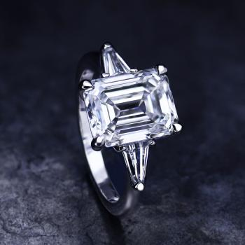 ring with an emerald cut diamond and two tapers on the side mounted on a thinner band
