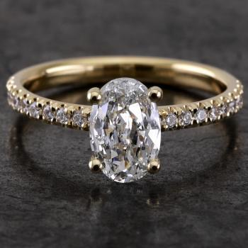 handmade solitaire ring with an oval cut diamond set in four prongs rounded setting made of round wire and the band set with smaller brilliants