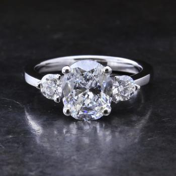 trilogy ring with a central oval cut diamond flanked by two brilliant cut diamonds