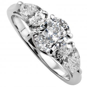 elegant and fine trilogy ring with a central oval cut diamond flanked by two pear shaped diamonds set with claws