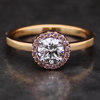 halo ring with a central brilliant cut diamond surrounded by smaller fancy light pink diamonds