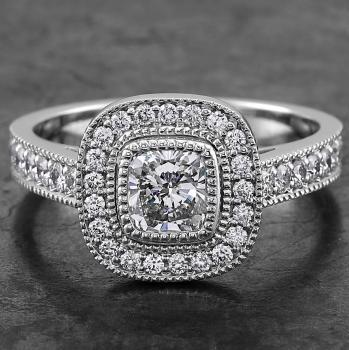 halo set ring with a cushion cut bezel set diamond surrounded by smaller brilliants flanked pavé set in boxes with millegrain finish wearable together with wedding band