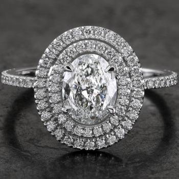 double entourage ring with an oval-cut diamond set with fine double prongs on a single fine band with rectangular profile castle pavé set with a row of smaller cut diamonds