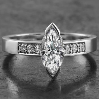 solitaire ring with a marquise cut diamond set in two corner prongs flanked by pavé set brilliant cut diamonds on a slim band with palmettes