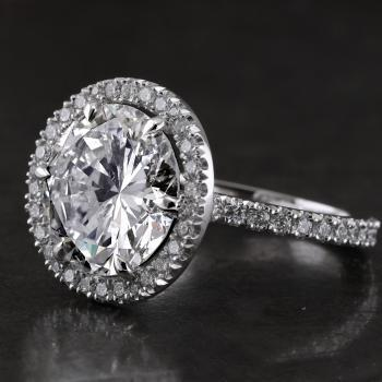 halo or entourage ring with a larger central brilliant cut diamond mounted on a band with a single V-construction with a rectangular profile for three fourths set with smaller diamonds (wearable with wedding rings)