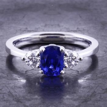 ring with a cushion cut sapphire and two brilliant cut diamonds on the side mounted on a thinner band