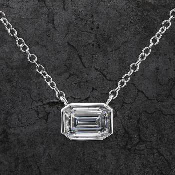 solitairenecklace with an emerald cut diamond besel set in a box with a thin border and fixed at anchor chain with extra rings at the end