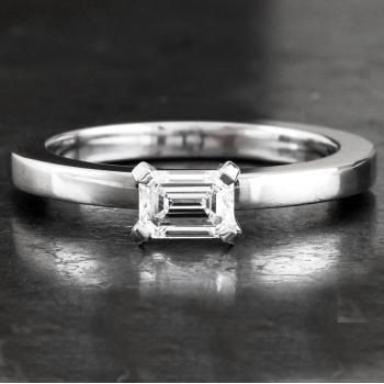solitaire ring with an emerald cut diamond low set in the same direction as the band in four prongs without without a middlering on a slim band with rectangular profile
