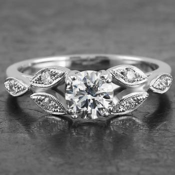 handmade soltaire ring with a brilliant cut diamond along which small marquise shaped leaves decorated with diamonds on a rounded band