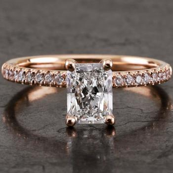 handmade engagement ring with a radiant cut diamond asymmetrically set with four curved prongs made with round wire and the band set with brilliant cut diamonds (can be worn together with a wedding ring)