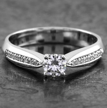 solitaire ring with a brilliant cut diamond set in four prongs and flanked by smaller diamonds on the band