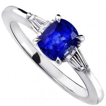 ring with a cushion cut sapphire and two tapered cut diamonds on the side mounted on a thinner band