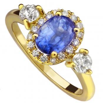 halo ring with an oval sapphire surrounded by smaller brilliant cut diamond flanked by two slightly larger diamonds adjacent to wedding ring