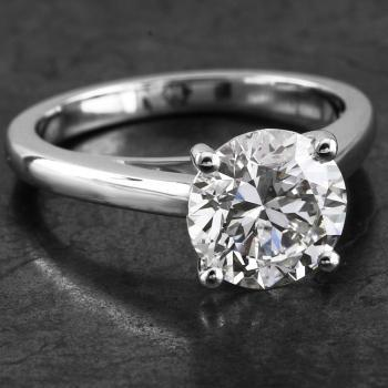 solitaire ring with a brilliant cut diamond set with four prongs on a thinner slightly rounded band with palmets