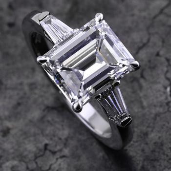 handmade ring with an emerald cut diamond and two tapers on the side mounted on a thinner band and set as low as possible