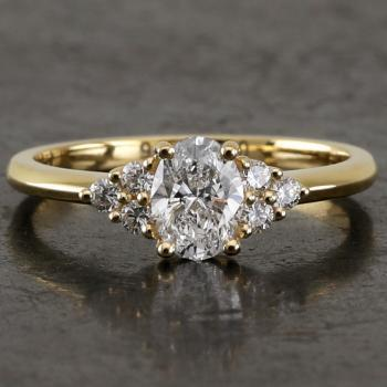 handmade ring with an oval diamond next to which three brilliant cut diamonds set with claws or prongs