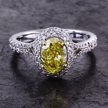 double halo ring with a central fancy yellow oval cut diamond surrounded by smaller castle pavé set brilliant cut diamonds