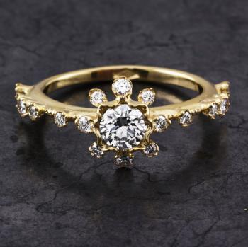 soltaire ring with a brilliant cut diamond along which small prong settings decorated with diamonds on a band finished with millegraine