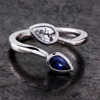 toi et moi ring with a pear cut diamond and a pear shaped sapphire bezel set in a closed basket
