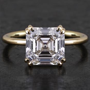 solitaire ring with an Asscher cut diamond set with four double prongs on a fine band with a round profile