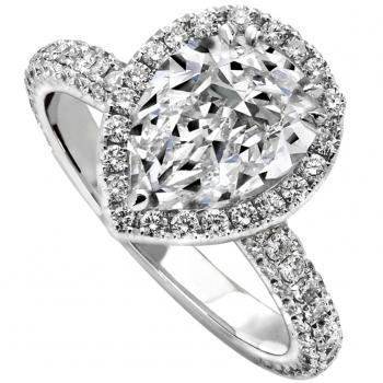 halo ring with a central pear cut diamond with tiny diamonds and the band castle set on top and on the side