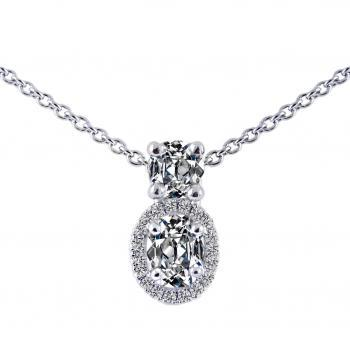 entourage pendant with an oval cut diamond around which smaller brilliants and above a cushion shaped diamond set in four prongs
