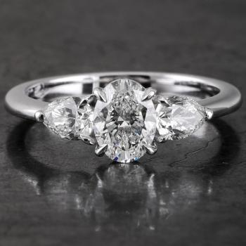 trilogy ring with an oval cut diamond set with four prongs, next to which two pear-cut diamonds