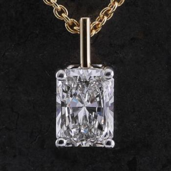 solitaire pendant with a radiant cut diamond set with four prongs mounted on a single fine bracket including fine anchor chain