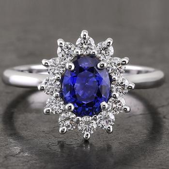 entourage ring with a central oval sapphire surrounded by brilliant cut diamonds set with prongs and wearable together with a rounded wedding band
