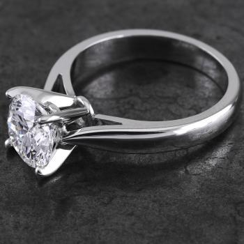 handmade solitaire ring with a larger central brilliant cut diamond set a little higher with four slim cut prongs on a band with slightly upward palmettes narrowing towards the top