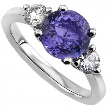 trilogy ring with a central tanzanite flanked by two brilliant cut diamonds