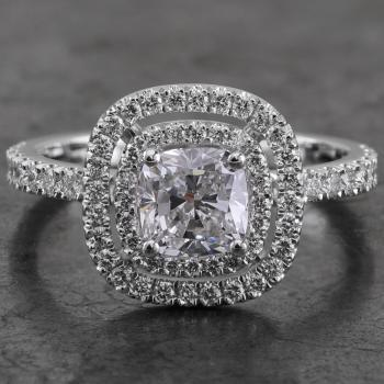 double entourage halo ring with with a cushion cut diamond set with fine prongs on a single band castle pavé set with one row of smaller brilliant cut diamonds