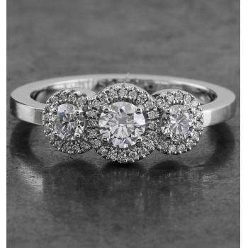entourage or halo ring with three central brilliants, the middle slightly larger and all surrounded by smaller pavé set diamonds mounted on a slim band with rectangular profile