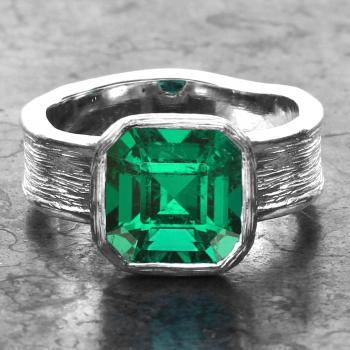 solitaire ring with a emerald cut emerald bezel set on an organic band with polished edges