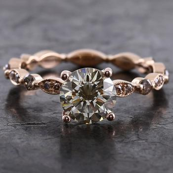 alliance ring with a larger olive greenish brown diamond set on a band with marquee pavé set with brown brilliants finished with millegraine and alternated with diamonds set with two claws