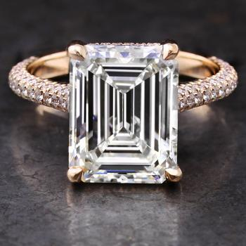 handmade solitaire ring with a central emerald cut diamond with drop shaped single prongs on a sideband set above and on the side with small brilliant cut diamonds