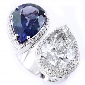toi-et-moi ring with pear shaped diamond and sapphire surrounded with smaller brillant cut pavé set diamonds