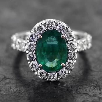 halo ring with a central oval cut emerald  on a single U supported entourage with castle pavé set diamonds