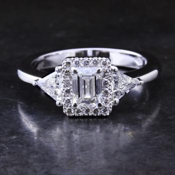 halo ring with an emerald cut diamond surrounded by brilliant cut diamonds flanked by two trilliant cut diamonds