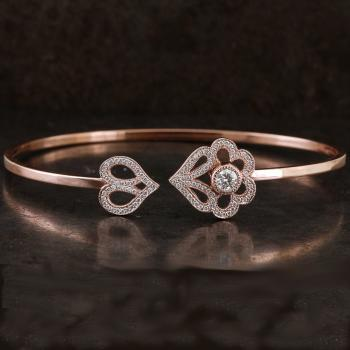 flexible esclave bracelet with arabeque hearts with a brilliant cut diamond set in a donut and surrounded with pavé set smaller brilliants all finished with millegrains and mounted on a hollow square profile