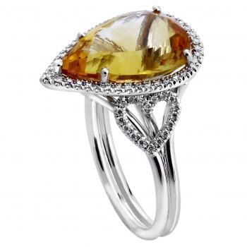 halo ring with a pear shaped citrine surrounded by small brilliant cut diamonds and flank by two set heart figures