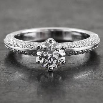 solitaire ring with a brilliant cut diamond set with six claws mounted between a band pavé set on both flanks with smaller diamonds
