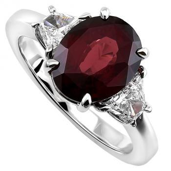 ring with an oval cut Red Garnet flanked by two trapeze shaped diamonds