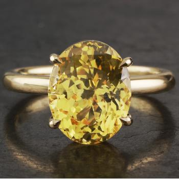 handmade solitaire ring with an oval cut yellow sapphire set with four single prongs on a fine band with a D-shaped profile