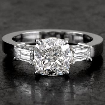 handmade ring with a central cushion cut diamond and two baguette cut diamonds mounted on a slim band