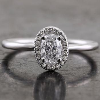 halo ring  with an oval cut diamond surrounded with smaller brilliant cut diamonds on an unset shank with a round profile